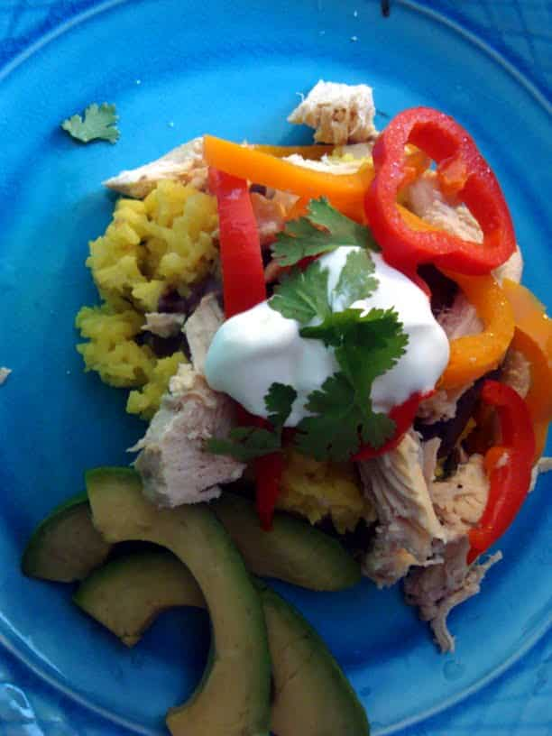 Make this easy chicken dish in the crock pot and serve with yellow rice for a delicious meal! Chicken Fiesta rice is a family favorite!