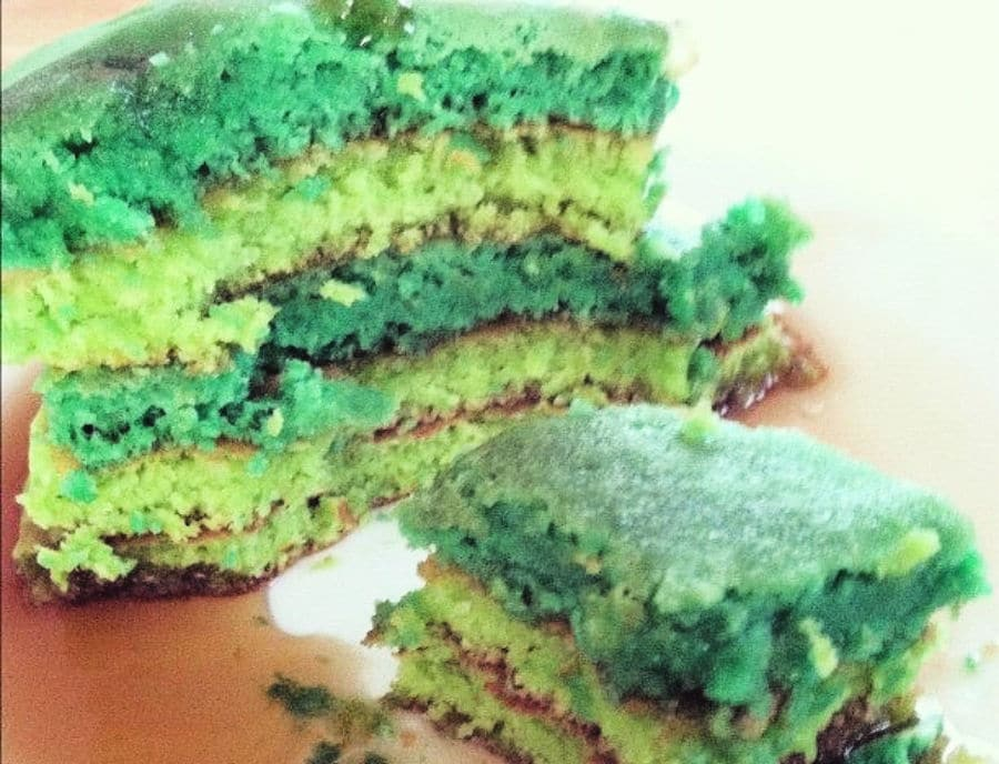 Green pancakes on a plate sliced down the middle
