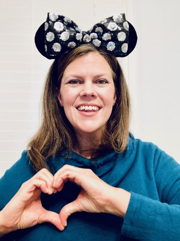 woman making heart with hands and wearing minnie ears