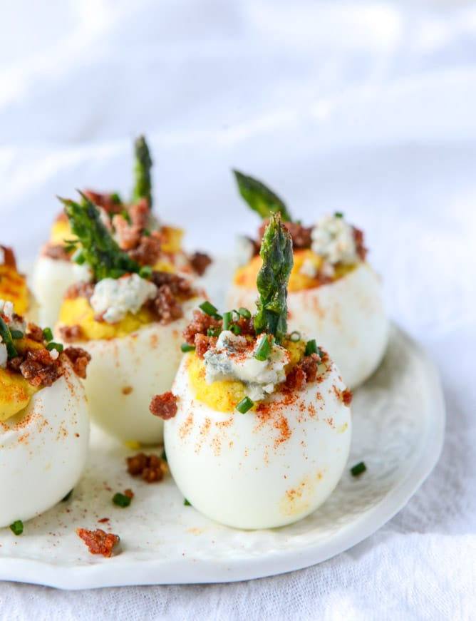 deviled eggs with asparagus on a plate