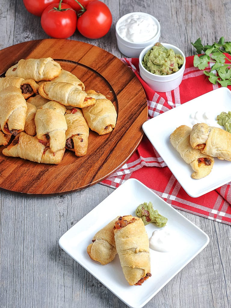 Crescent Roll Empanadas on platter and servings on plates with toppings