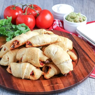 Empanadas on platter with plates and toppings next to them