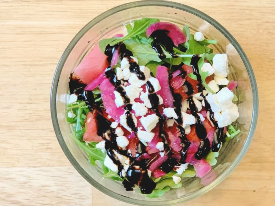 watermelon arugula salad with balasamic glaze in a glass bowl