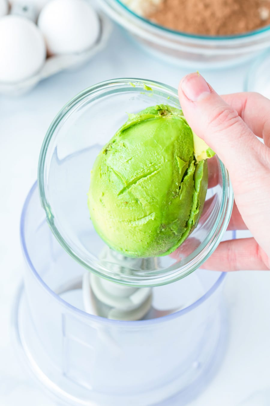 a hand holding a peeled avocado in a bowl