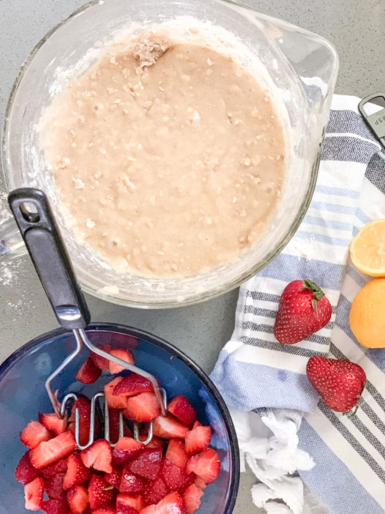 Make easy recipes with strawberries like this quick bread batter in a bowl with fresh strawberries about to be mixed in.