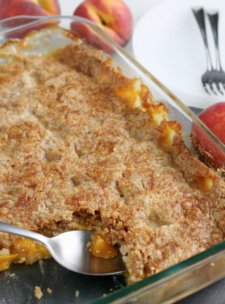 freshly baked peach dump cake with serving spoon