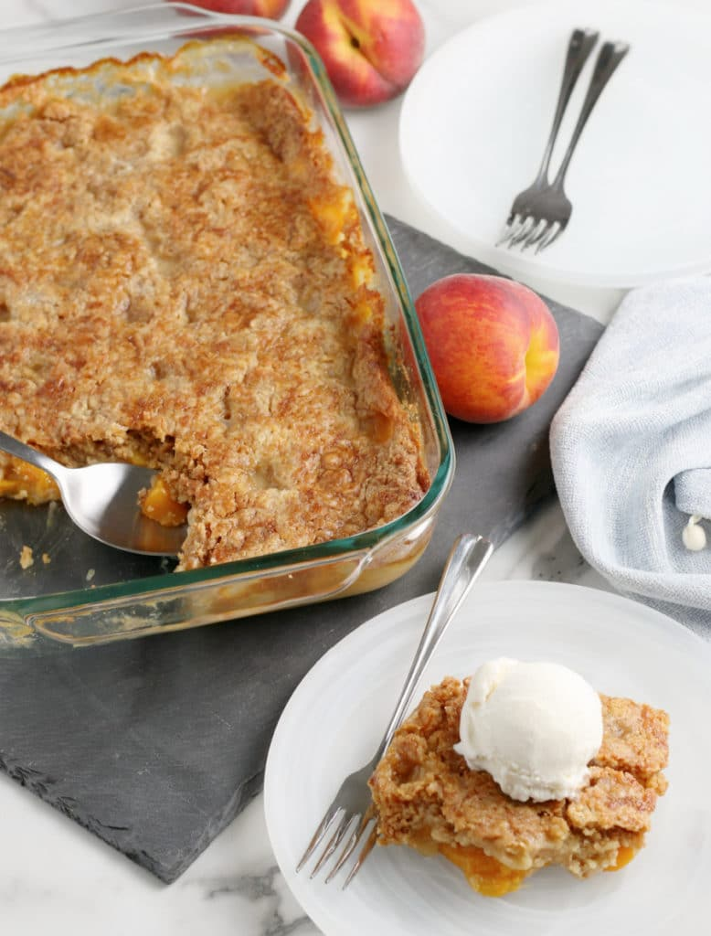 peach dump cake in pan and slice on plate with scoop of vanilla ice cream