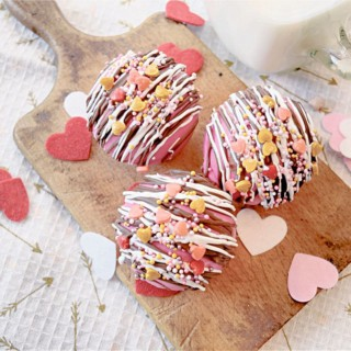 cocoa bombs pink with sprinkles on a wood board