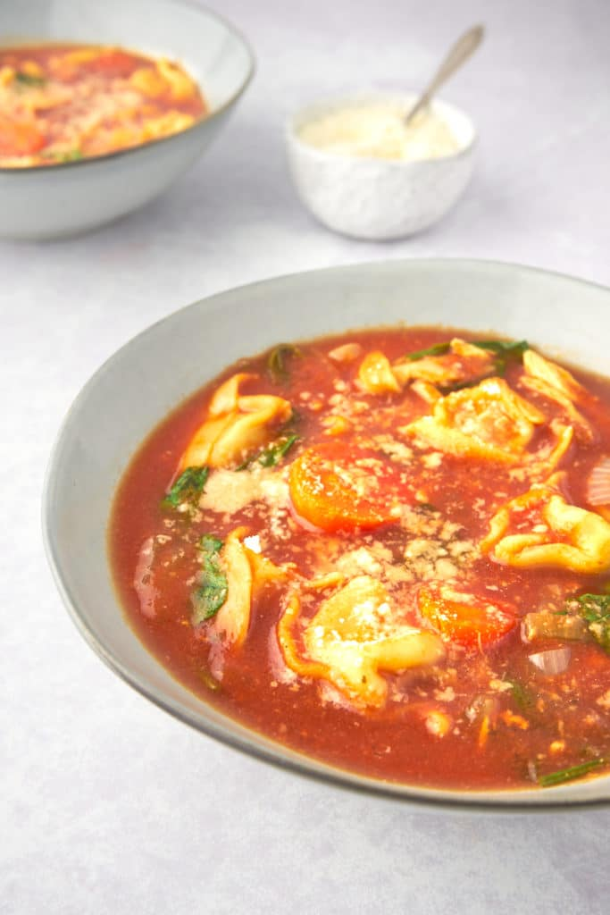 tomato tortellini soup with chicken and spinach in a bowl with parmesan on top
