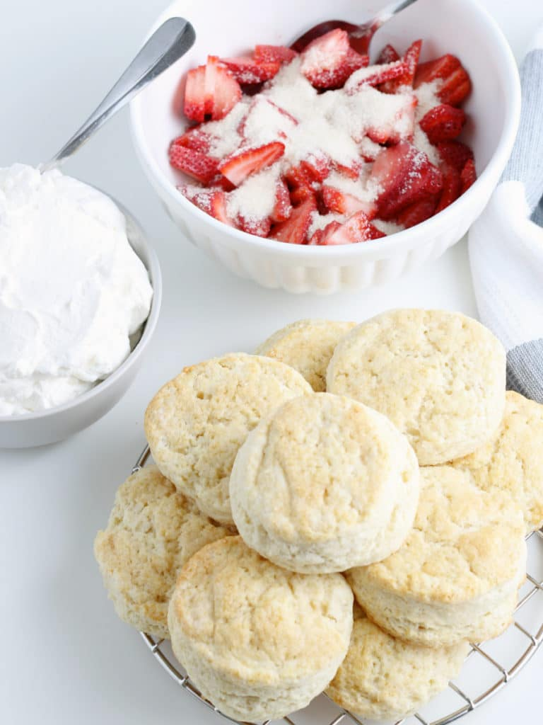 strawberries with sugar in bowl with stack of shortcakes