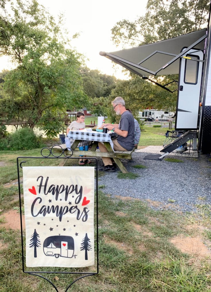 Happy RV Campers flag with family eating near RV in the background
