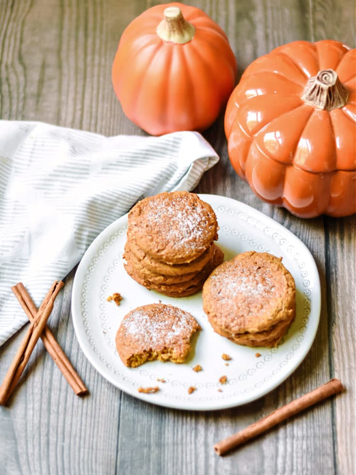 Pumpkin Spice Cookies with sugar on top on a plate in a fall scene with pumpkins and cinnamon sticks