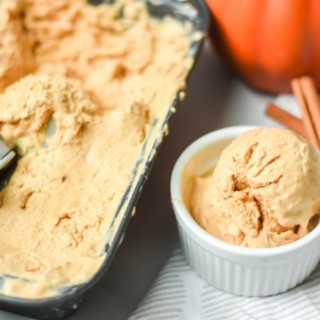 Scoop of pumpkin ice cream in bowl with full pan of ice cream