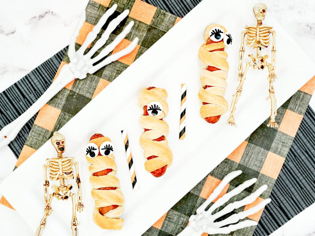 Mummy dogs recipe on a platter with decorative skeletons